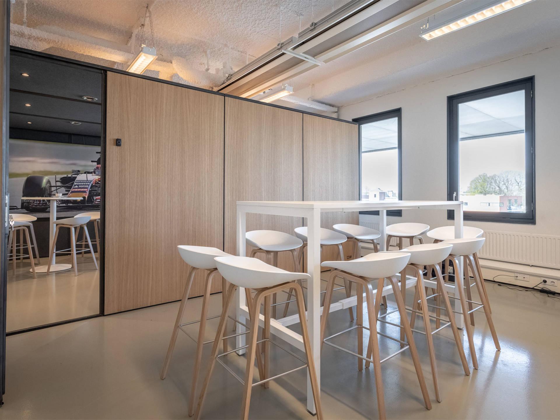 Buiten de meetingbox vind je een aanlandtafel met bijpassende barkrukken van het merk HAY.